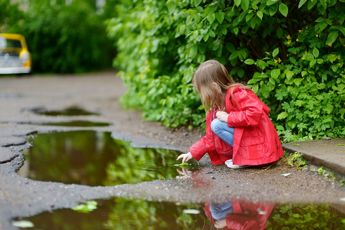 Adorable girl playing in a puddle on rainy summer day