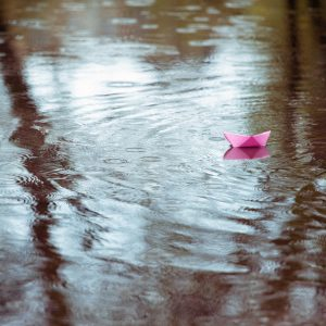 pink paper boat in a puddle in the rain