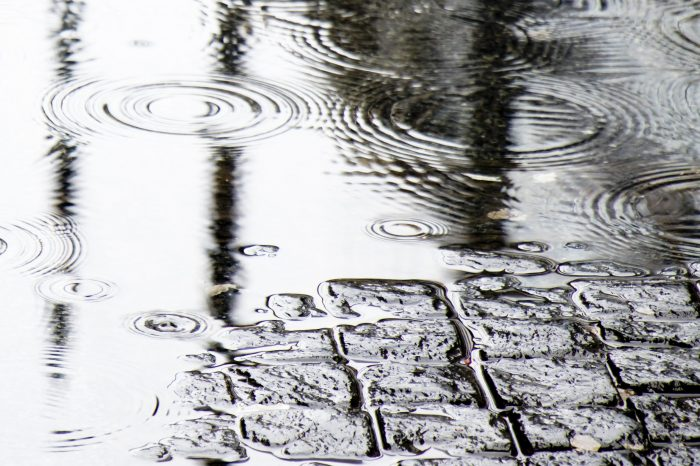 Detail of  rain drops in a puddle and reflections on a cobbled road
